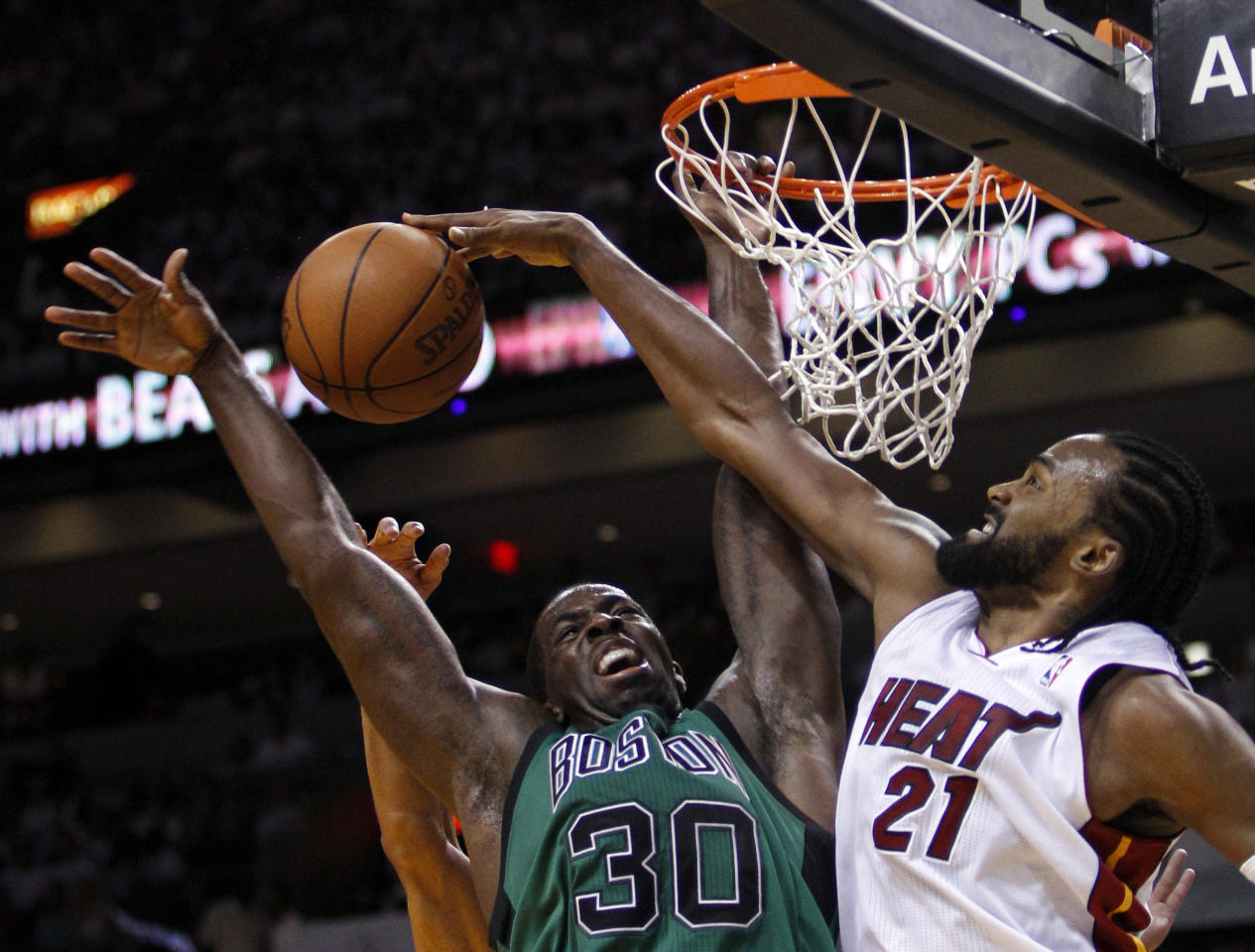 Miami Heat's Ronny Turiaf (21) blocks a shot by Boston Celtics' Brandon Bass (30) during the second half of Game 1 in their NBA basketball Eastern Conference finals playoffs series, Monday May, 28, 2012, in Miami. (AP Photo/Lynne Sladky)