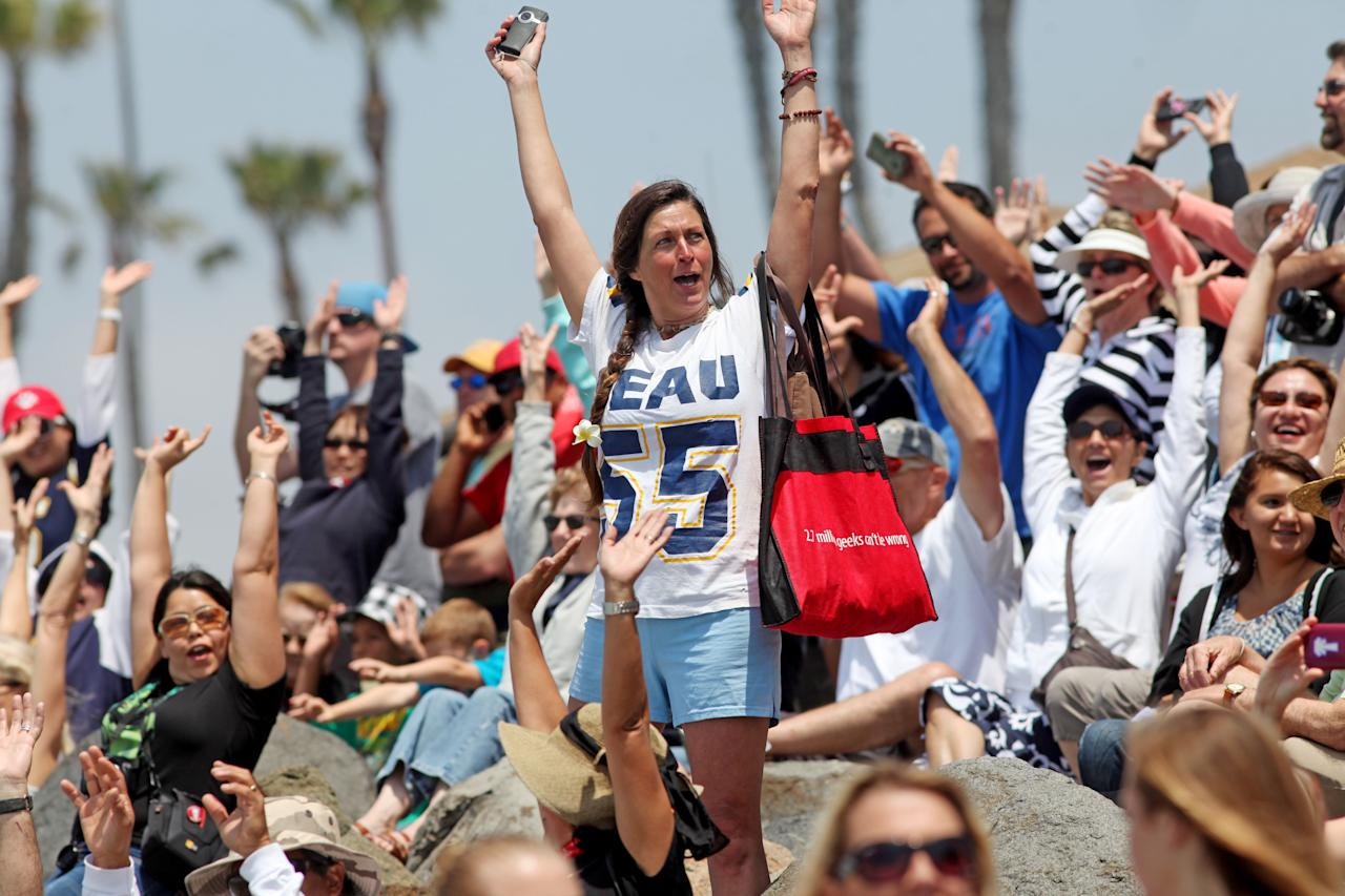 """OCEANSIDE, CA - MAY 6: Bryn Best waves to surfers in the water during a """"paddle-out"""" ceremony in honor of NFL star Junior Seau on May 6, 2012 in Oceanside, California.  Seau, who played for various NFL teams including the San Diego Chargers, Miami Dolphins and New England Patriots was found dead in his home on May 2nd of an apparent suicide.  Family members have decided to donate his brain for research on links between concussions and possible depression. (Photo by Sandy Huffaker/Getty Images)"""