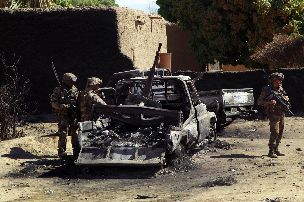 French troops inspect the charred remains of military vehicles used by radical Islamists on the outskirt of Diabaly, Mali, some 460kms (320 miles) north of the capital Bamako Monday Jan. 21, 2013. French and Malian troops were in the city whose capture by radical Islamists prompted the French military intervention. (AP Photo/Jerome Delay)