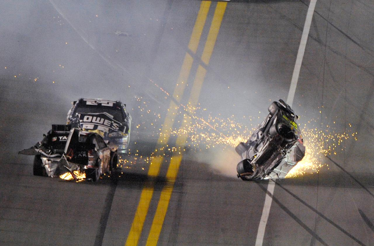 Jeff Gordon, right, flips over after colliding with Kurt Busch, left, as Jimmie Johnson drives behind Busch during the NASCAR Budweiser Shootout auto race at Daytona International Speedway, Saturday, Feb. 18, 2012, in Daytona Beach, Fla. (AP Photo/Phelan M. Ebenhack)