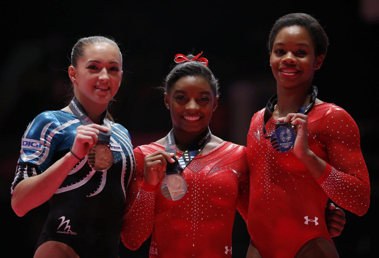 Gold medalist Simone Biles (C) of the U.S poses with silver medalist Gabrielle Douglas (R) of the U.S and Larisa Andreea Iordache of Romania after the women's all-round final at the World Gymnastics Championships at the Hydro Arena in Glasgow, Scotland, October 29, 2015.   REUTERS/Phil Noble