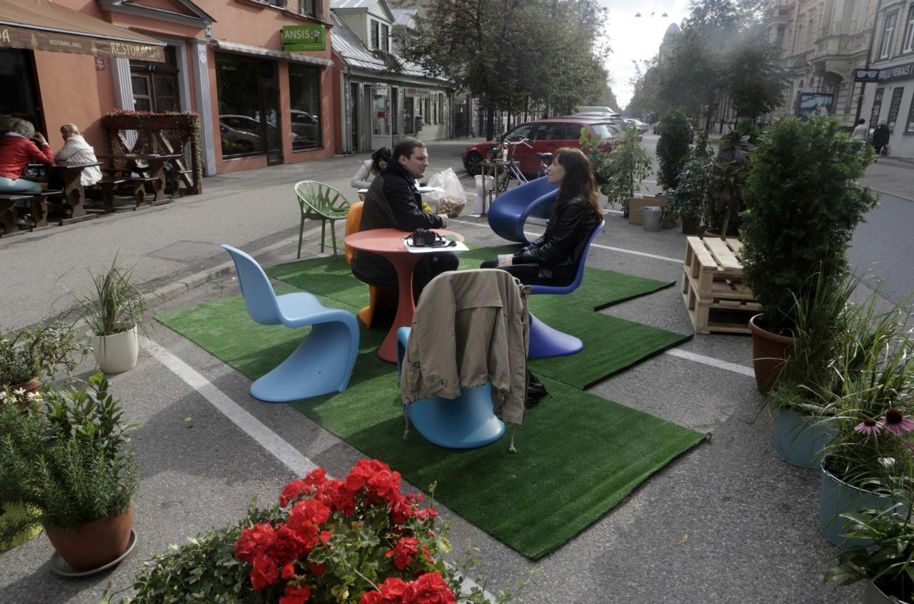 People sit on chairs during a PARK(ing) Day event in Riga, September 20, 2013. The event aims to transform metered parking spaces into temporary public places to call attention to the need for more urban open spaces and discuss the creation and allocation of public spaces, according to organizers. REUTERS/Ints Kalnins (LATVIA - Tags: SOCIETY)