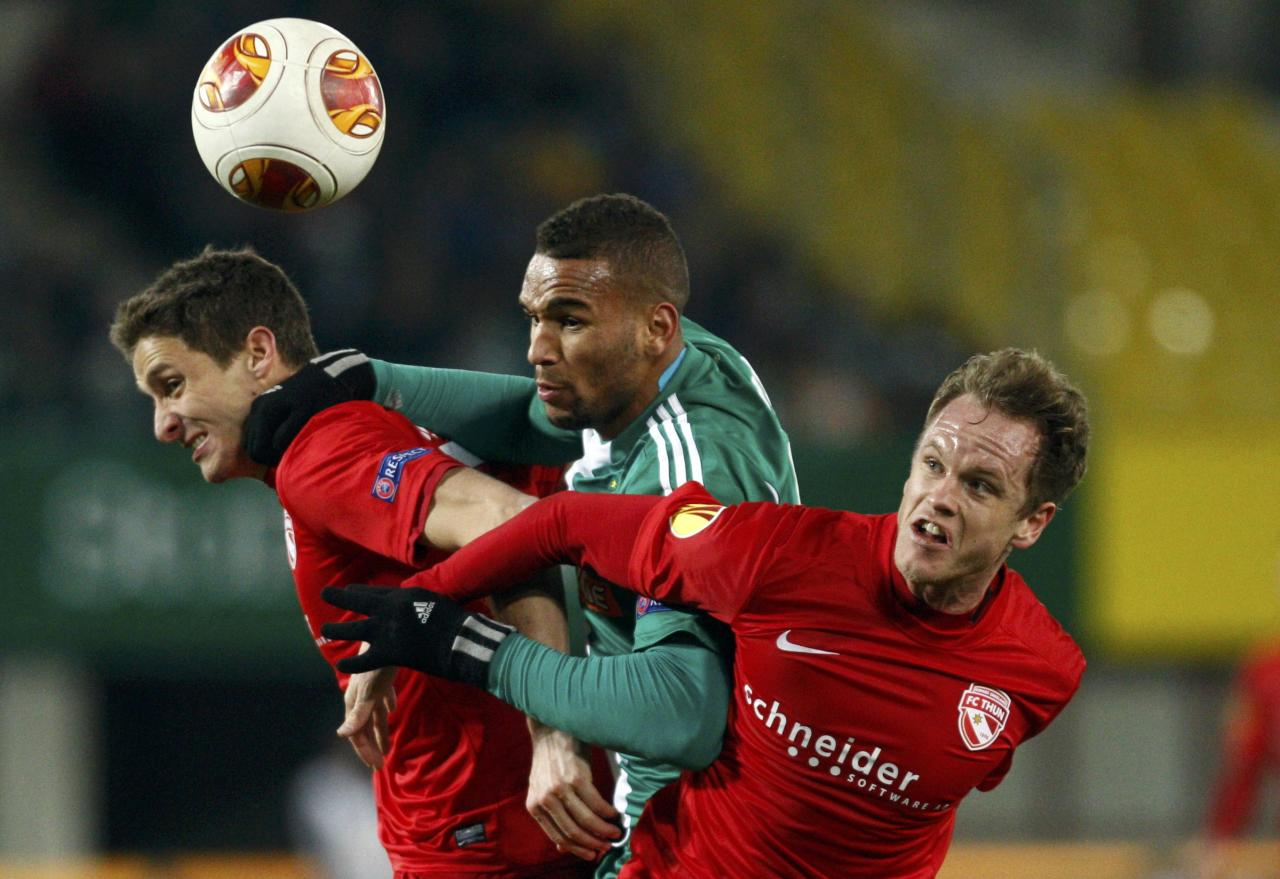 Fulvio Sulmoni (L) and Lukas Schenkel (R) of FC Thun challenge Terrence Boyd of Rapid Vienna (C) for a high ball during their Europa League soccer match in Vienna November 28, 2013. REUTERS/Heinz-Peter Bader (AUSTRIA - Tags: SPORT SOCCER TPX IMAGES OF THE DAY)