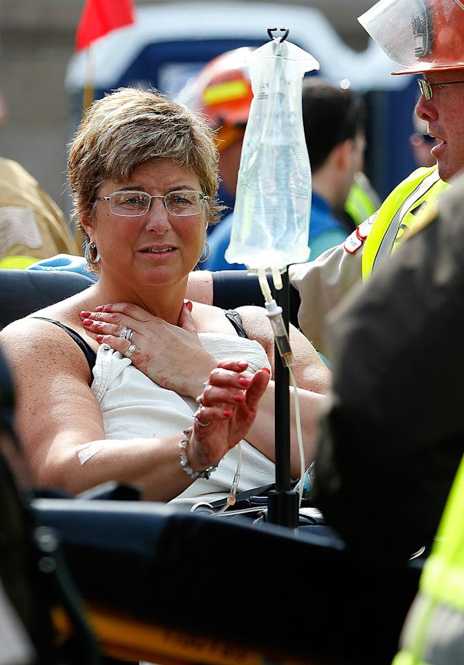 BOSTON, MA - APRIL 15:  A woman looks at the blood on her hands as she is loaded into an ambulance after being injured after two bombs exploded on the marathon route on April 15, 2013 in Boston, Massachusetts. Two people are confirmed dead and at least 23 injured after two explosions went off near the finish line to the marathon. (Photo by Jim Rogash/Getty Images)