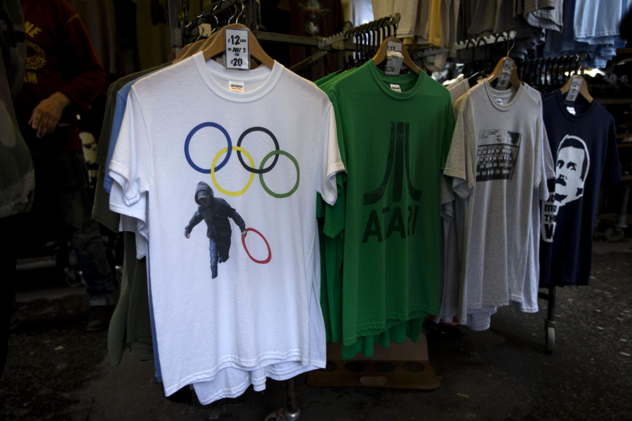 <p>               In this photo taken Monday, July 16, 2012, a t-shirt depicting a rioter holding an Olympic ring is displayed on sale in a London market. The guardians of the games are vigilant about protecting the integrity - and the commercial clout - of the Olympic brand. But even they can't stop the irreverent spirit of artists and craftspeople, who have responded to the games with a cheeky mix of celebration, skepticism and satire. (AP Photo/Matt Dunham)