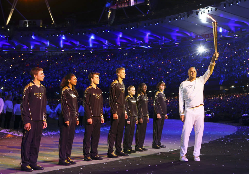 Steve Redgrave, right, holds up the Olympic flame after entering the stadium during the Opening Ceremony at the 2012 Summer Olympics, Saturday, July 28, 2012, in London. (AP Photo/Cameron Spencer, Pool)