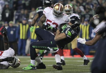 Seattle Seahawks Kearse falls on the leg of San Francisco 49ers NaVorro Bowman as he loses control of the ball during the fourth quarter in the NFL's NFC Championship football game in Seattle