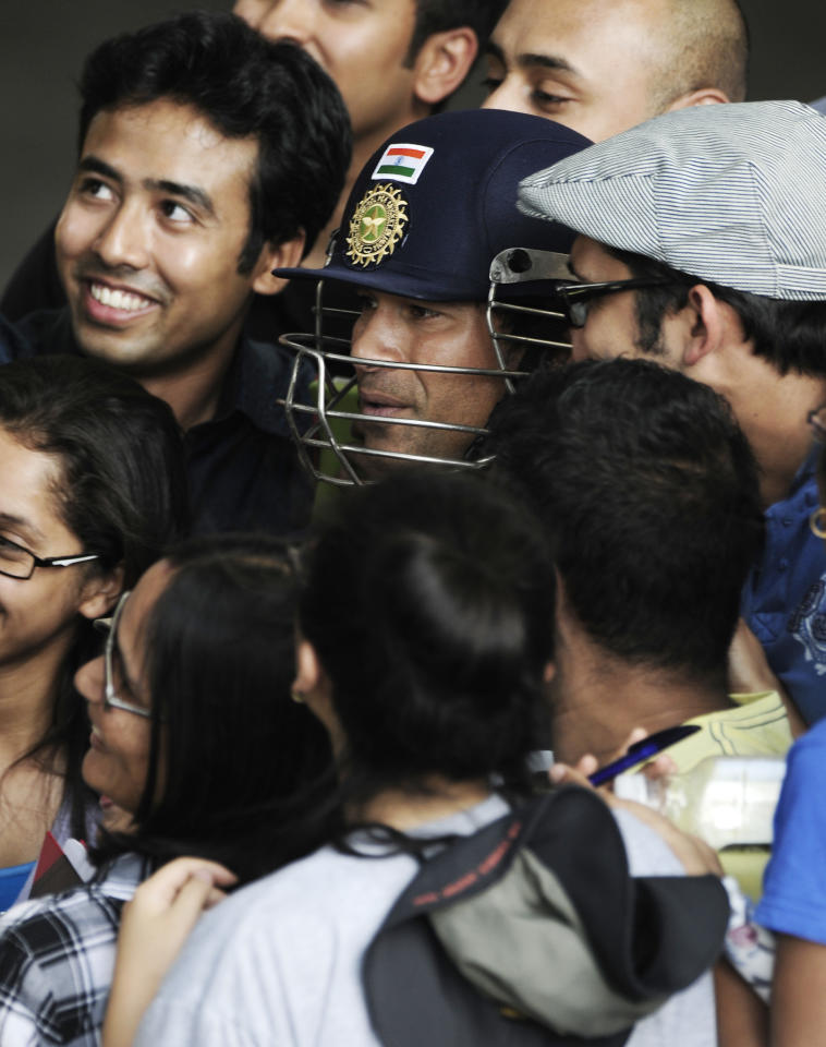 India's Sachin Tendulkar poses with fans before he prepares for training at the nets prior to the opening day of cricket against Australia in Adelaide, Australia, Monday, Jan. 23, 2012. (AP Photo/David Mariuz)