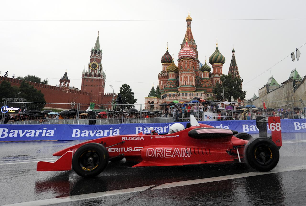 "Russia's racing driver Natalie Freidina drives past St. Basils cathedral during the ""Moscow City Racing"" show on July 17, 2011 in central Moscow. AFP PHOTO / NATALIA KOLESNIKOVA (Photo credit should read NATALIA KOLESNIKOVA/AFP/Getty Images)"
