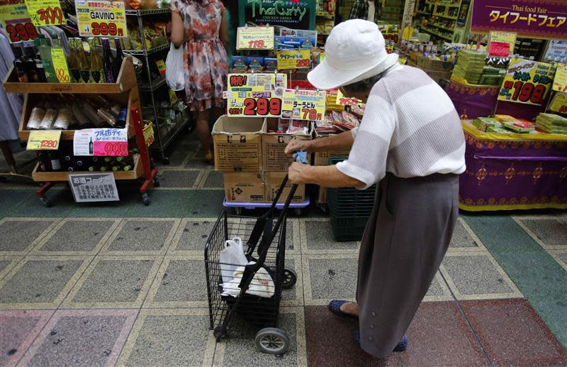 File photo of a woman pushing a cart looking at items at a local shopping street in Tokyo