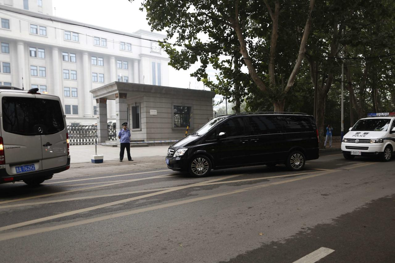 A minivan (C) believed to be carrying disgraced Chinese politician Bo Xilai arrives at the Jinan Intermediate People's Court, in Jinan, Shandong province September 22, 2013. A Chinese court will announce its verdict on former top politician Bo on Sunday following his 5-day trial last month on charges of corruption and abuse of power. He could be handed a long jail term by the Communist Party-controlled court. REUTERS/Aly Song (CHINA - Tags: POLITICS CRIME LAW)