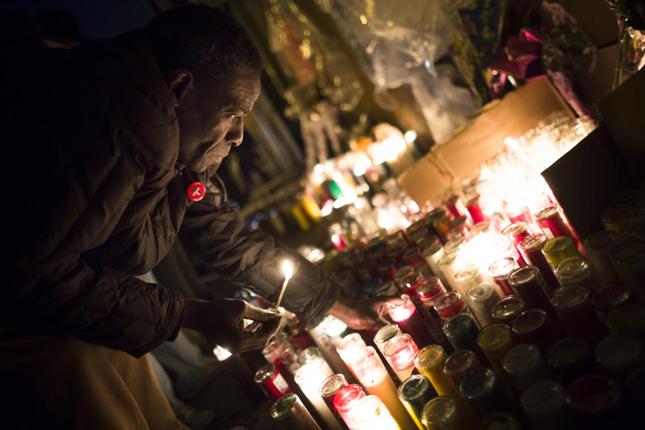 """Evan Brown, 53, lights candles during a vigil held for Kimani """"Kiki"""" Gray in the East Flatbush neighborhood of Brooklyn, Wednesday, March 13, 2013, in New York. The 16-year-old was shot to death on a Brooklyn street last Saturday night by plainclothes police officers who claim the youth pointed a .38-caliber revolver at them. (AP Photo/John Minchillo)"""