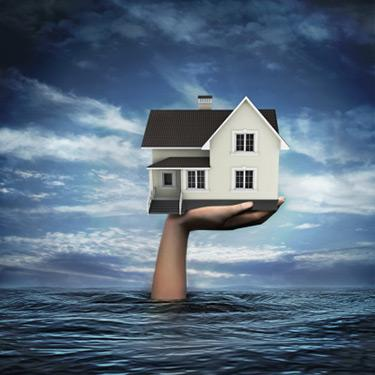 Illustrative-image-of-hand-coming-out-from-sea-holding-model-home_web