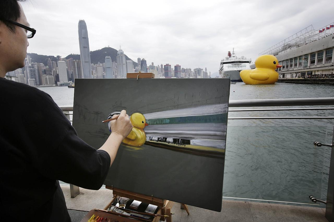 "HONG KONG - MAY 02: A man paints Dutch conceptual artist, Florentijin Hofman's Floating duck sculpture called ""Spreading Joy Around the World"" as it arrives in Victoria Harbour on May 2, 2013 in Hong Kong. The ""Rubber Duck"", which is 16.5 meters high, will be in Hong Kong from May 2 to June 9. Since 2007, ""Rubber Duck"" has been traveling to 10 countries and 12 cities. (Photo by Jessica Hromas/Getty Images)"