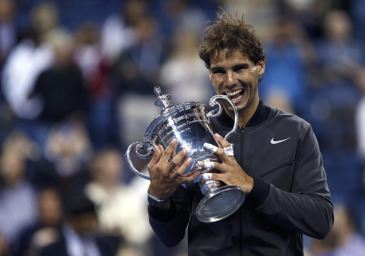 Rafael Nadal of Spain bites his trophy after defeating Novak Djokovic of Serbia in their men's final match at the U.S. Open tennis championships in New York, September 9, 2013. REUTERS/Eduardo Munoz (UNITED STATES - Tags: SPORT TENNIS)