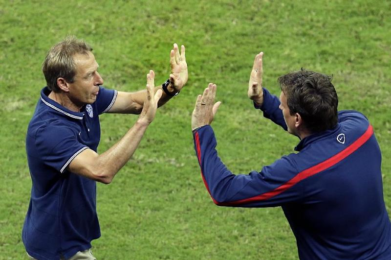 United States' head coach Juergen Klinsmann celebrates with a staff member after Jermaine Jones scored his side's first goal during the group G World Cup soccer match between the USA and Portugal at the Arena da Amazonia in Manaus, Brazil, Sunday, June 22, 2014
