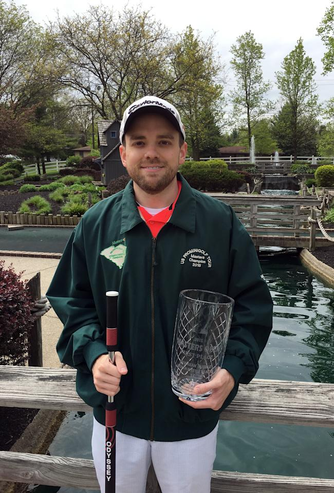 <p> In this photo taken May 3, 2016, Matt Male poses in Westerville, Ohio, with the green windbreaker and crystal vase he won by placing first in the professional putting's version of the Masters tournament. (AP Photo/Mitch Stacy </p>