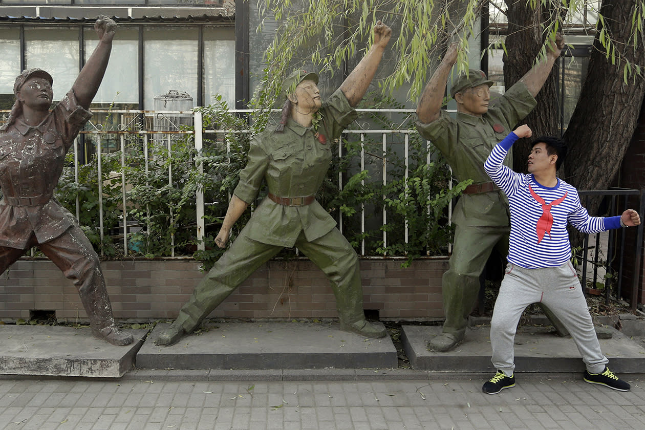 A man tries to mimic the gesture of military sculptures while he poses for photos.