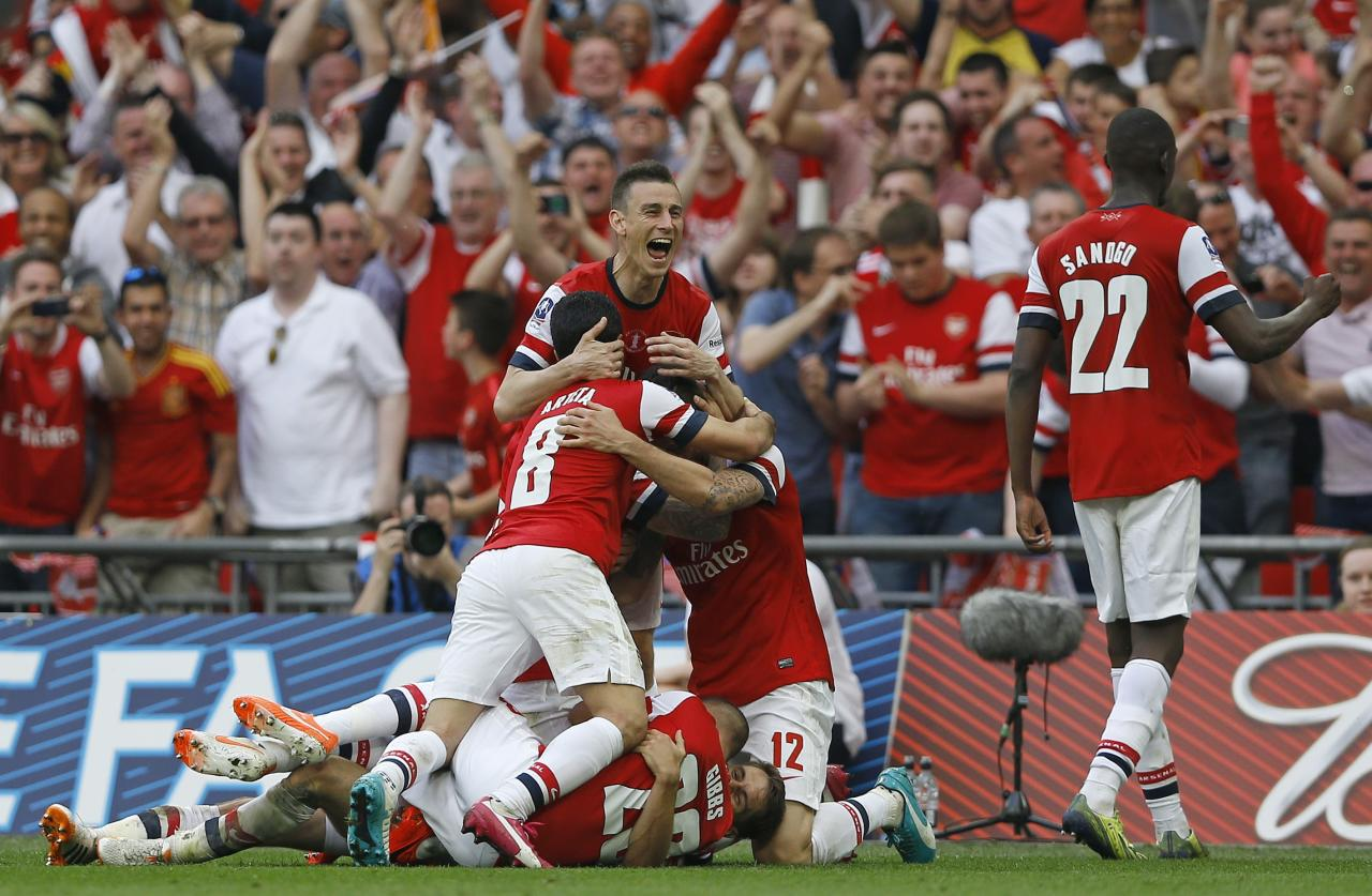 Arsenal players celebrates after Aaron Ramsey scored his sides 3rd goal during the English FA Cup final soccer match between Arsenal and Hull City at Wembley Stadium in London, Saturday, May 17, 2014. (AP Photo/Kirsty Wigglesworth)