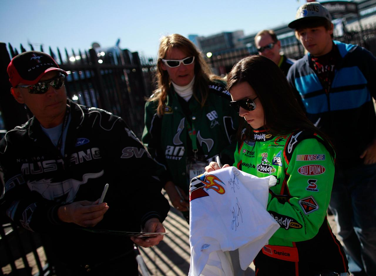 FORT WORTH, TX - NOVEMBER 04:  Danica Patrick, driver of the #7 GoDaddy.com/DanWheldonMemorial.com Chevrolet in the Nationwide Series, signs an autograph during practice for the NASCAR Sprint Cup Series AAA Texas 500 at Texas Motor Speedway on November 4, 2011 in Fort Worth, Texas.  (Photo by Tom Pennington/Getty Images for NASCAR)