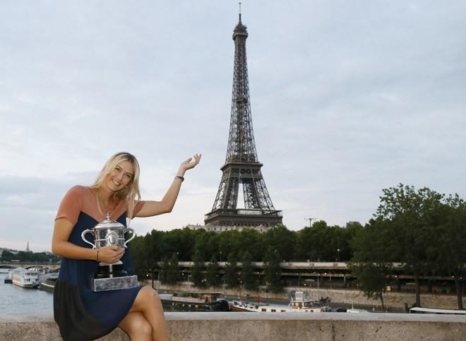 TOPSHOTS Russian tennis player Maria Sharapova poses with her trophy in front the Eiffel tower on June 9, 2012 in Paris, after winning the Women's Singles final tennis match of the French Open tennis tournament at the Roland Garros stadium.  AFP PHOTO / PATRICK KOVARIKPATRICK KOVARIK/AFP/GettyImages