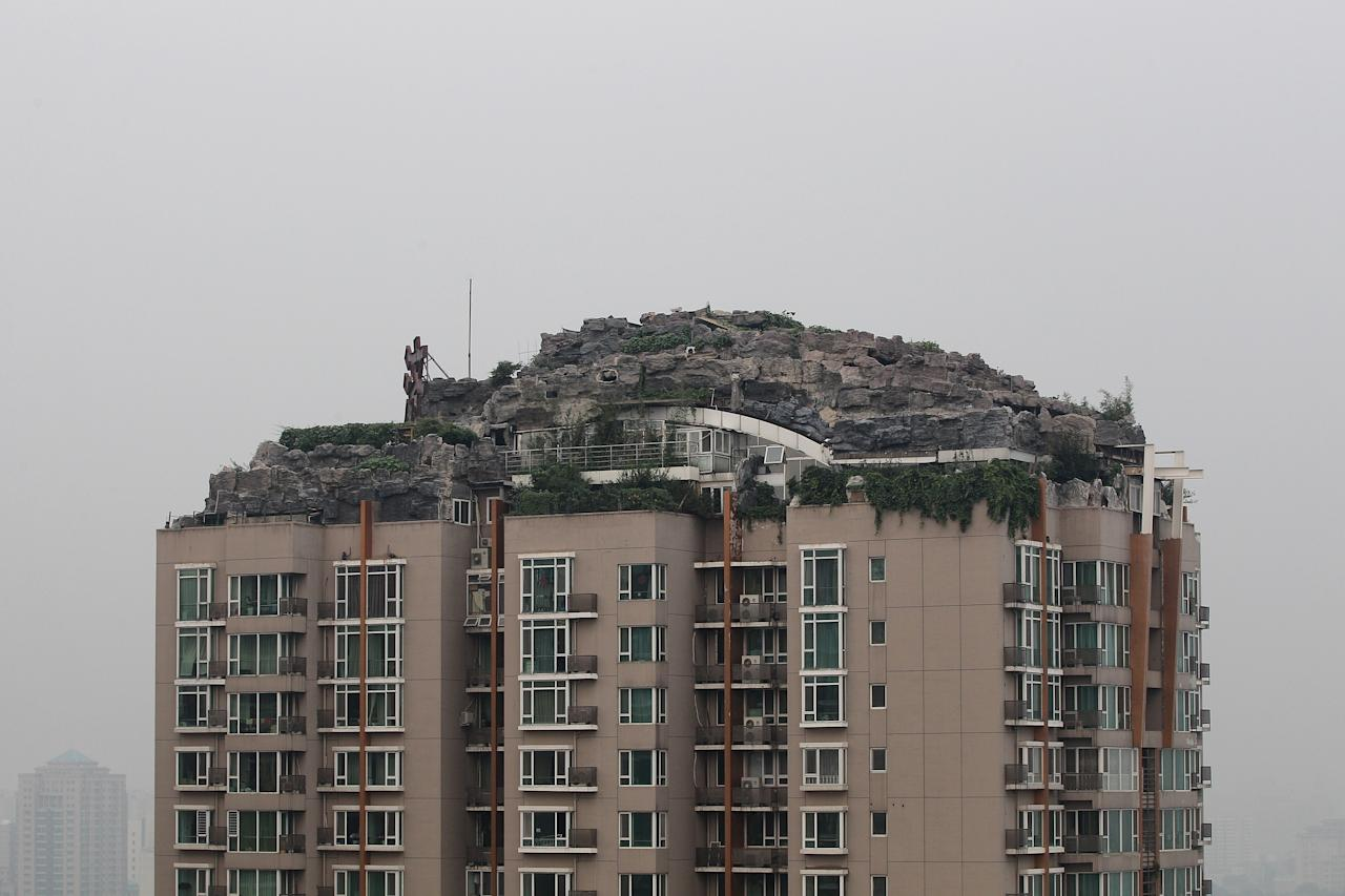 BEIJING, CHINA - AUGUST 15: A general view of the mountain peak and luxury villa on the top of a 26-floor residential building on August 15, 2013 in Beijing, China. A medicine mogul spent six years building his own private mountain peak and luxury villa on the top of residential building. Beijing authorities urged the owner to demolish the illegal building within 15 days. (Photo by Feng Li/Getty Images)