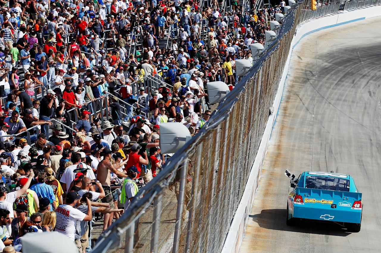DOVER, DE - JUNE 03:  Jimmie Johnson, driver of the #48 Lowe's Madagascar Chevrolet, celebrates with the checkered flag after winning the NASCAR Sprint Cup Series FedEx 400 benefiting Autism Speaks at Dover International Speedway on June 3, 2012 in Dover, Delaware.  (Photo by Todd Warshaw/Getty Images)