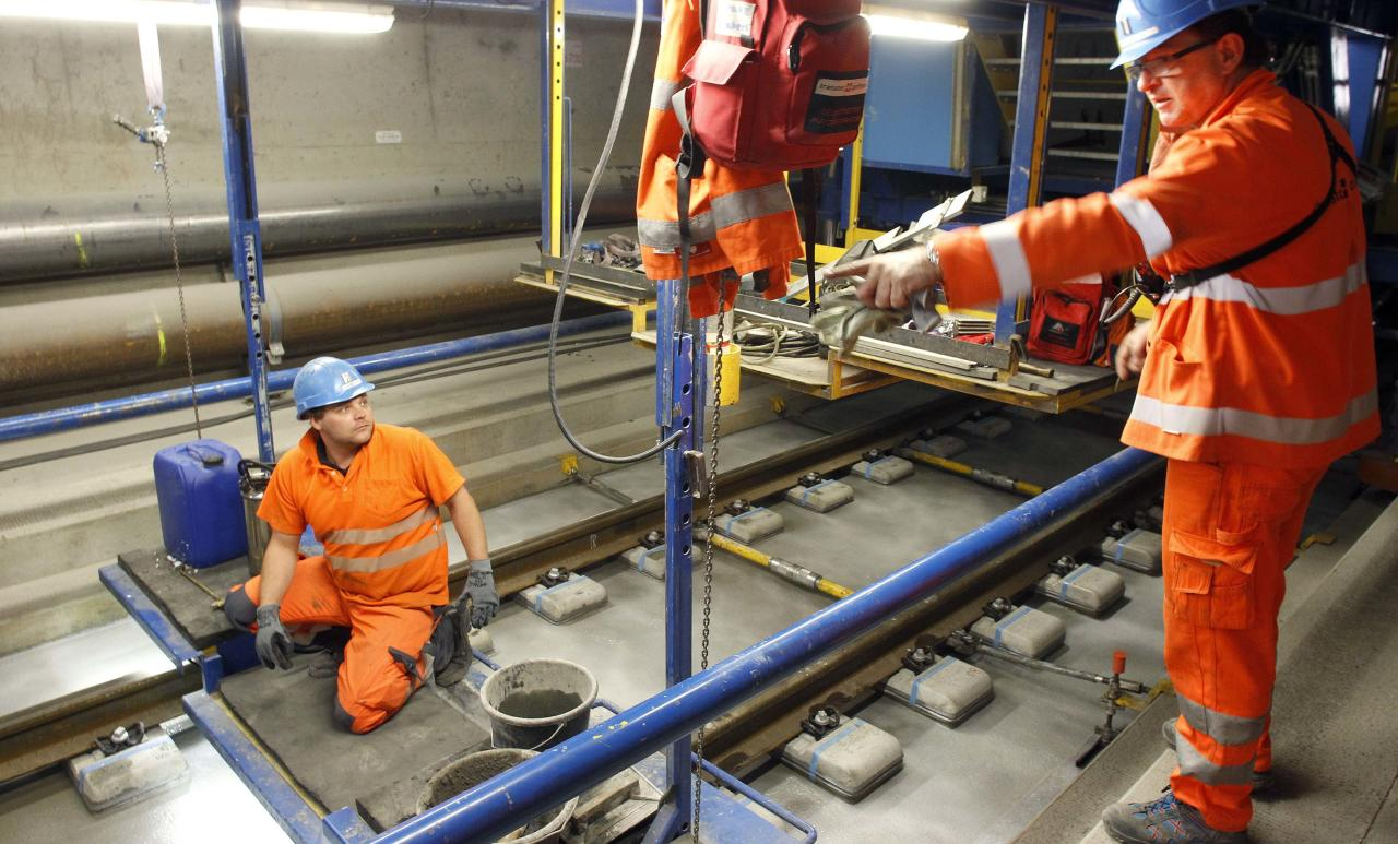 A worker receives instructions from an engineer during the installation of the railway tracks in the NEAT Gotthard Base tunnel near Erstfeld May 7, 2012. Crossing the Alps, the world's longest train tunnel should become operational at the end of 2016. The project consists of two parallel single track tunnels, each of a length of 57 km (35 miles)  REUTERS/Arnd Wiegmann   (SWITZERLAND - Tags: BUSINESS CONSTRUCTION EMPLOYMENT TRAVEL)