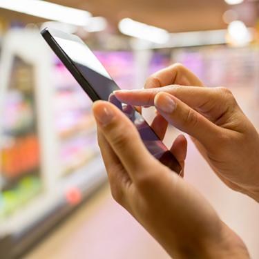 Woman-using-mobile-phone-while-shopping-in-supermarket_web