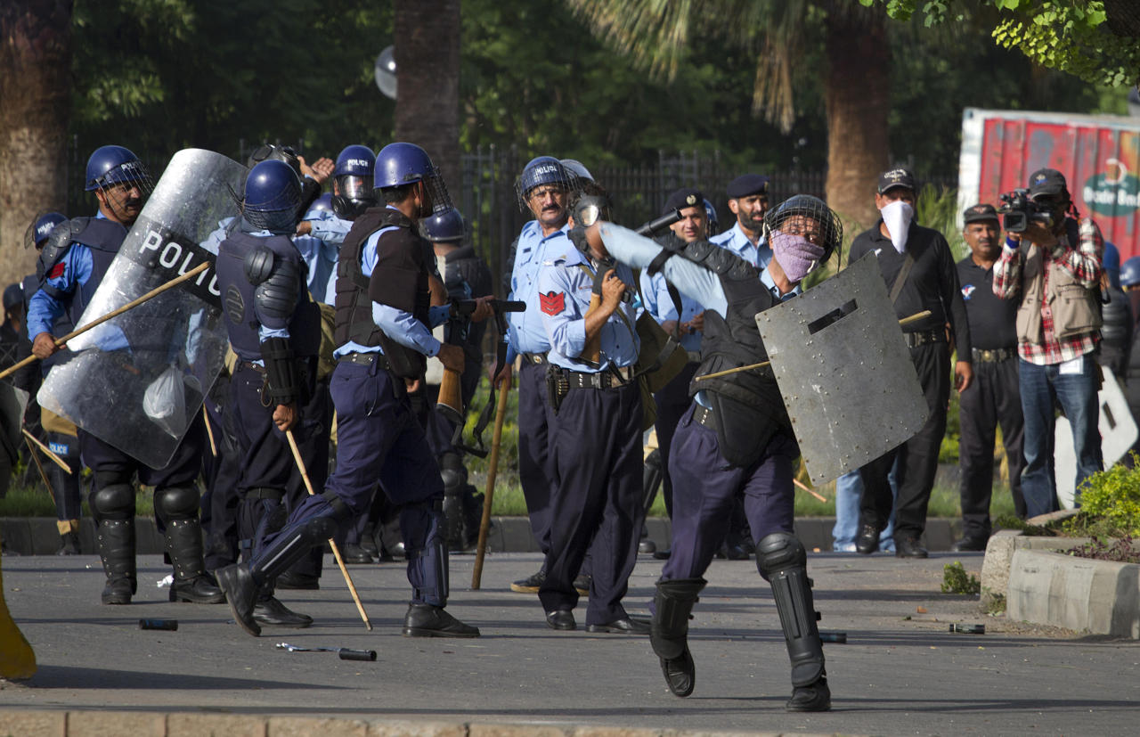 A Pakistani police officer throws stone as others prepare to fire tear gas at protesters during clashes that erupted as protestors tried to approach the U.S. embassy, Friday, Sept. 21, 2012 in Islamabad, Pakistan. Protests by tens of thousands of Pakistanis infuriated by an anti-Islam film descended into deadly violence on Friday, with police firing tear gas and live ammunition in an attempt to subdue rioters who hurled rocks and set fire to buildings in some cities. Four people were killed and dozens injured on a holiday declared by Pakistan's government so people could rally against the video. (AP Photo/Anjum Naveed)