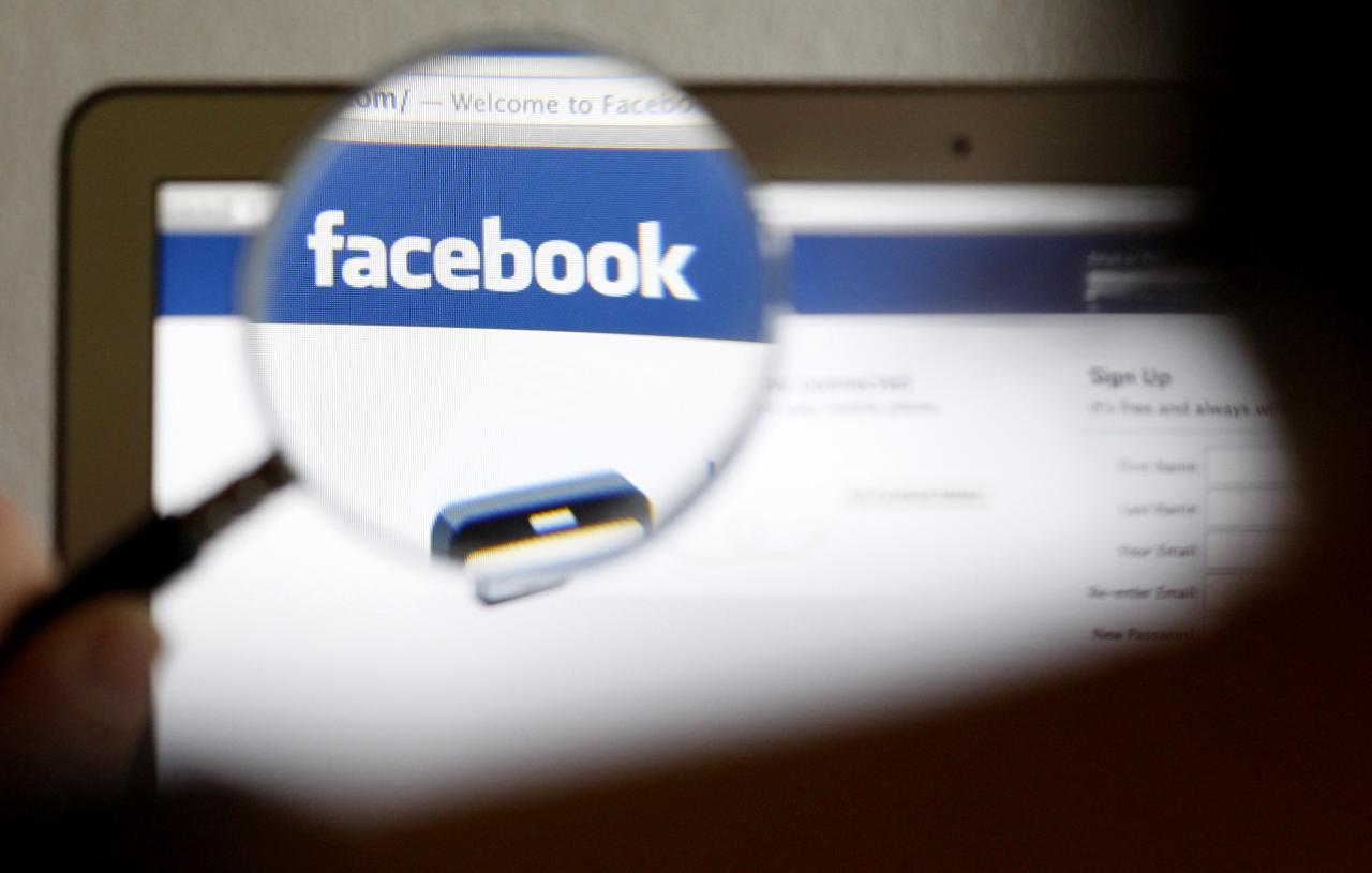 In this photo illustration, a Facebook logo on a computer screen is seen through a magnifying glass held by a woman in Bern in this May 19, 2012, file photo. Facebook Inc's revenue rose 32 percent in the third quarter to $1.26 billion, October 23, 2012.  REUTERS/Thomas Hodel/Files  (SWITZERLAND - Tags: SOCIETY SCIENCE TECHNOLOGY BUSINESS)