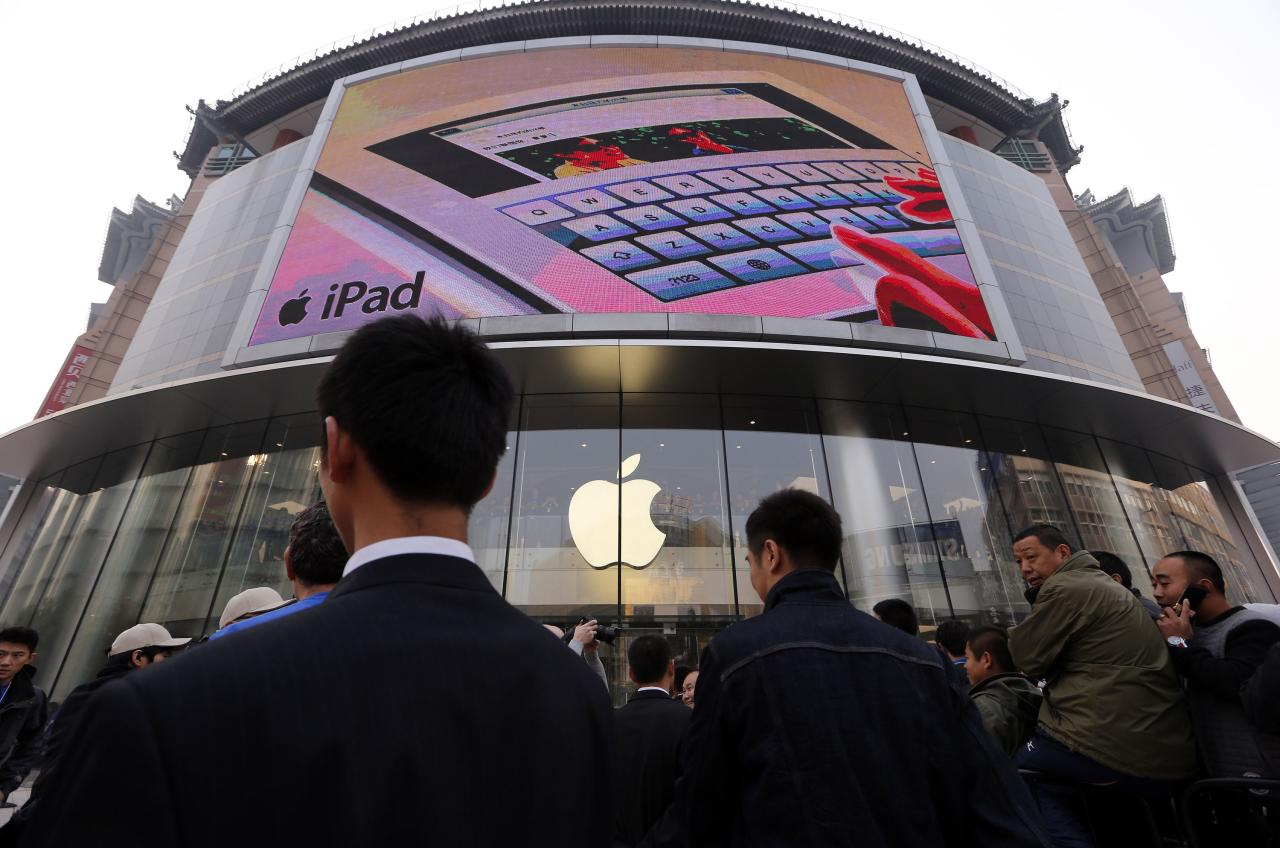 Security staff watch over a crowd gathered for the opening of a new Apple store in Beijing's Wangfujing shopping district October 20, 2012. The store is Apple's fifth in mainland China, as is being promoted as the largest in Asia.     REUTERS/David Gray     (CHINA - Tags: BUSINESS)