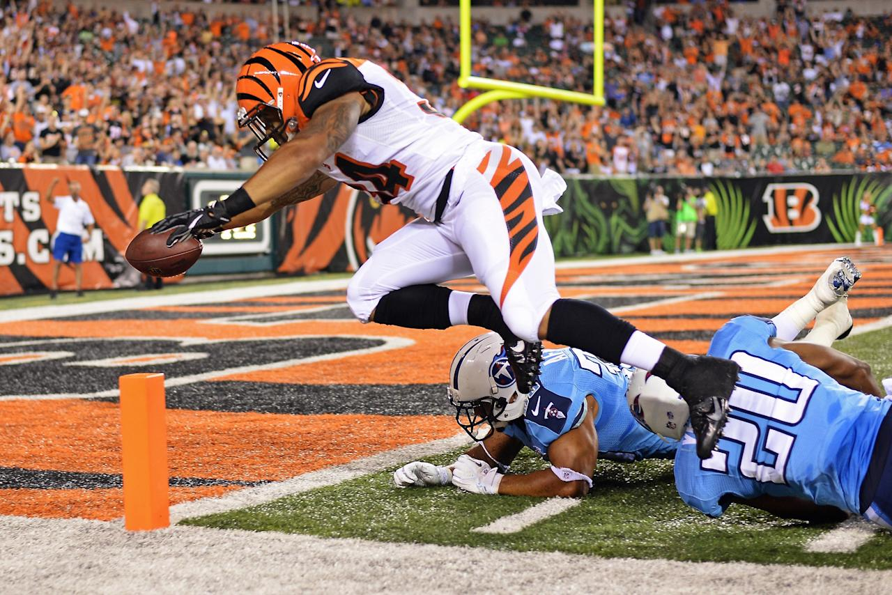 CINCINNATI, OH - AUGUST 17: Dan Herron #34 of the Cincinnati Bengals leaps in to the end zone to complete a 40-yard touchdown run past Al Afalava #38 of the Tennessee Titans and Alterraun Verner #20 of the Tennessee Titans in the fourth quarter at Paul Brown Stadium on August 17, 2013 in Cincinnati, Ohio. Cincinnati defeated Tennessee 24-19. (Photo by Jamie Sabau/Getty Images)