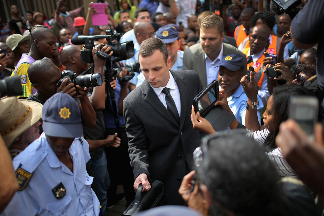 PRETORIA, SOUTH AFRICA - MARCH 07: Oscar Pistorius is surrounded by police and media as he leaves North Gauteng High Court after the fifth day of his trial on March 7, 2014 in Pretoria, South Africa. Olympic and Paralympic athlete Oscar Pistorius, aged 27, is accused of murdering his girlfriend Reeva Steenkamp. Pistorius denies the allegation claiming he mistook Steenkamp for an intruder inside their home on Valentines Day 2013. (Photo by Christopher Furlong/Getty Images)