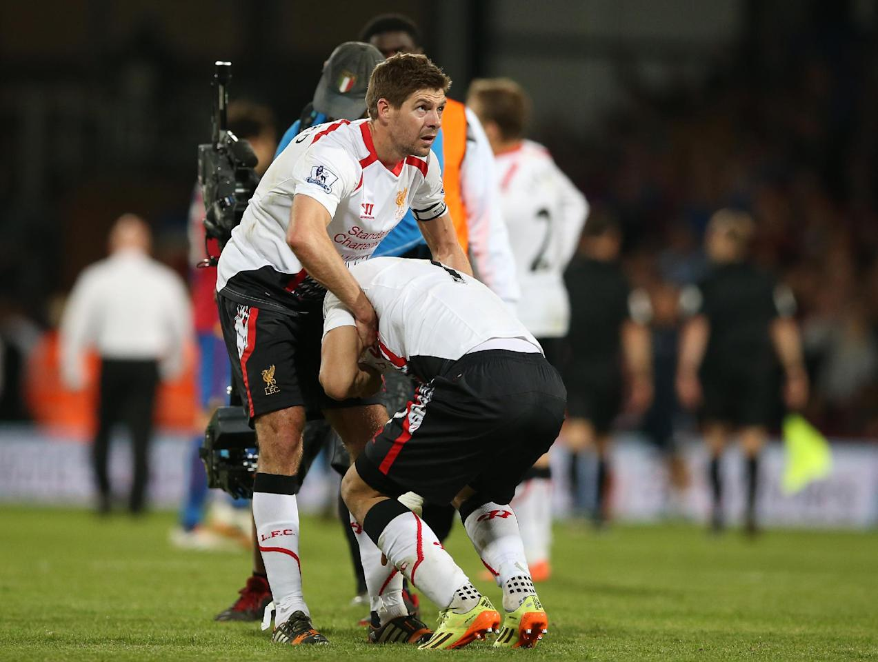 Liverpool's Steven Gerrard, left helps teammate Luis Suarez, following the end of the English Premier League soccer match between Crystal Palace and Liverpool at Selhurst Park stadium in London, Monday, May 5, 2014. The game ended in a 3-3 draw. (AP Photo/Alastair Grant)