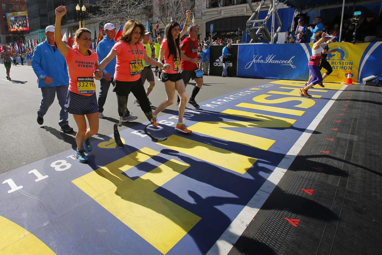 2013 Boston Marathon survivors Celeste (2nd L) and Sydney Corcoran (C) cross the finish line with Celeste's sister Carmen Acabbo, who ran the 118th Boston Marathon in Boston, Massachusetts April 21, 2014. REUTERS/Brian Snyder (UNITED STATES - Tags: SPORT ATHLETICS TPX IMAGES OF THE DAY)