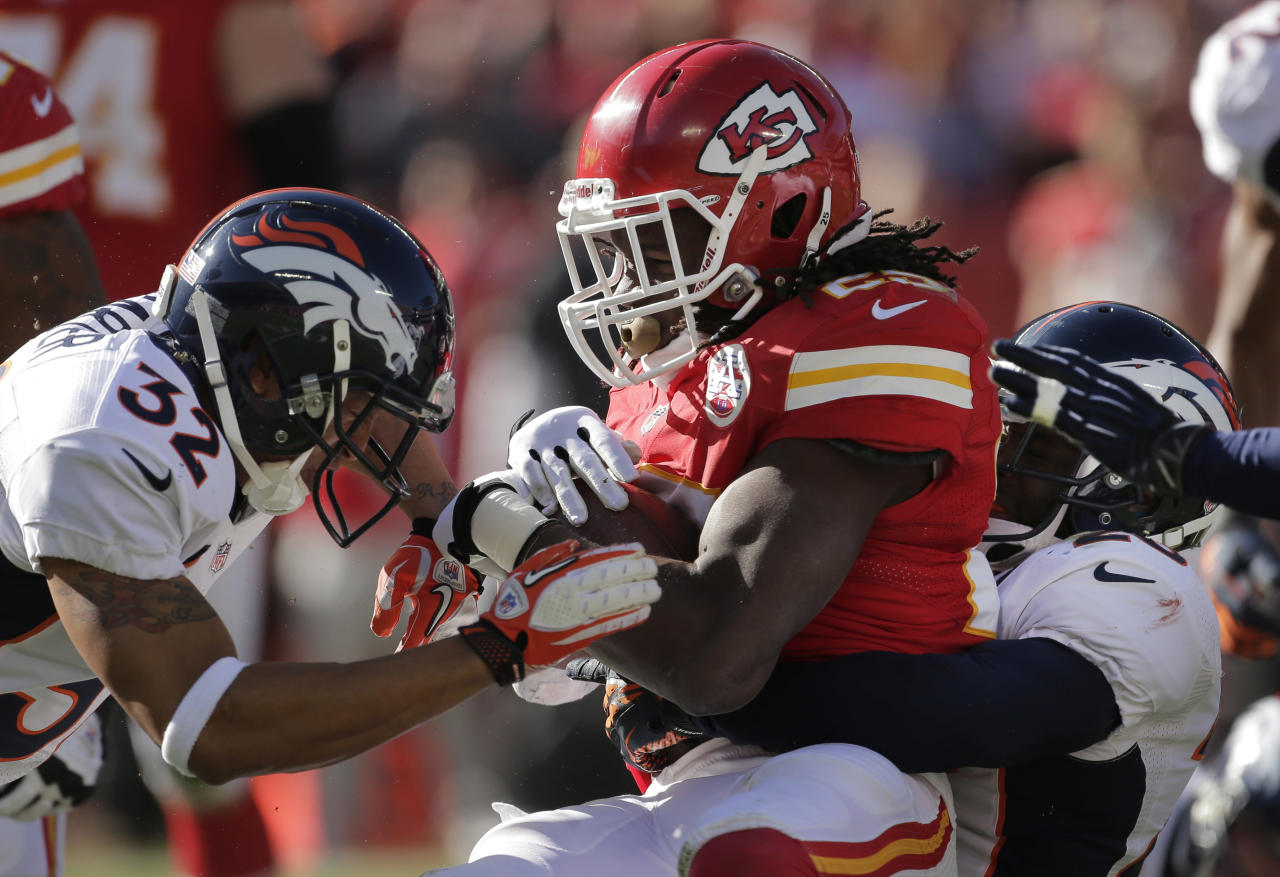 Kansas City Chiefs running back Jamaal Charles (25) is tackled by Denver Broncos strong safety Mike Adams, right, and defensive back Tony Carter (32) during the first half of an NFL football game at Arrowhead Stadium in Kansas City, Mo., Sunday, Nov. 25, 2012. (AP Photo/Charlie Riedel)
