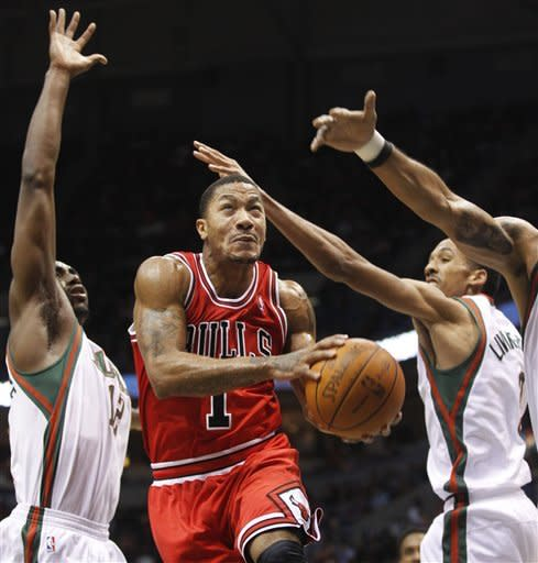Chicago Bulls' Derrick Rose (1) drives the basket against Milwaukee Bucks' Luc Richard Mbah a Moute, left, and Shaun Livingston, right, during the second half of an NBA basketball game Saturday, Feb. 4, 2012, in Milwaukee. (AP Photo/Jeffrey Phelps)