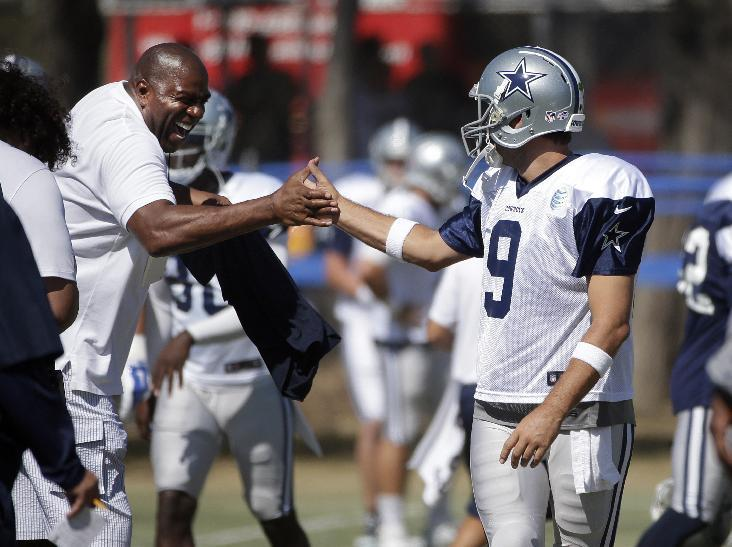 Los Angeles Dodgers part-owner Magic Johnson, left, and Dallas Cowboys quarterback Tony Romo shake hands before the team's joint football practice with the Oakland Raiders on Tuesday, Aug. 12, 2014, in Oxnard, Calif