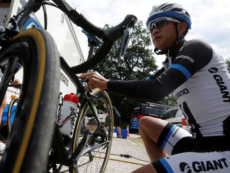 FILE PHOTO: Team Giant-Shimano rider Ji Cheng of China checks his bicycle after a training session for the Tour de France cycling race near Leeds, Britian, July 4, 2014.      REUTERS/Christian Hartmann/File Photo