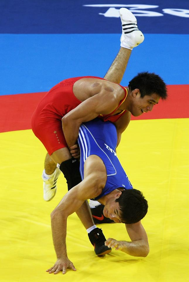 BEIJING - AUGUST 13:  Darkhan Bayakhmetov (blue) of Kazakhstan is thrown by Li Yanyan (red) of China in the Men's Greco-Roman 66kg quarter final bout at the China Agriculture University Gymnasium during Day 5 of the Beijing 2008 Olympic Games on August 13, 2008 in Beijing, China.  (Photo by Clive Rose/Getty Images)