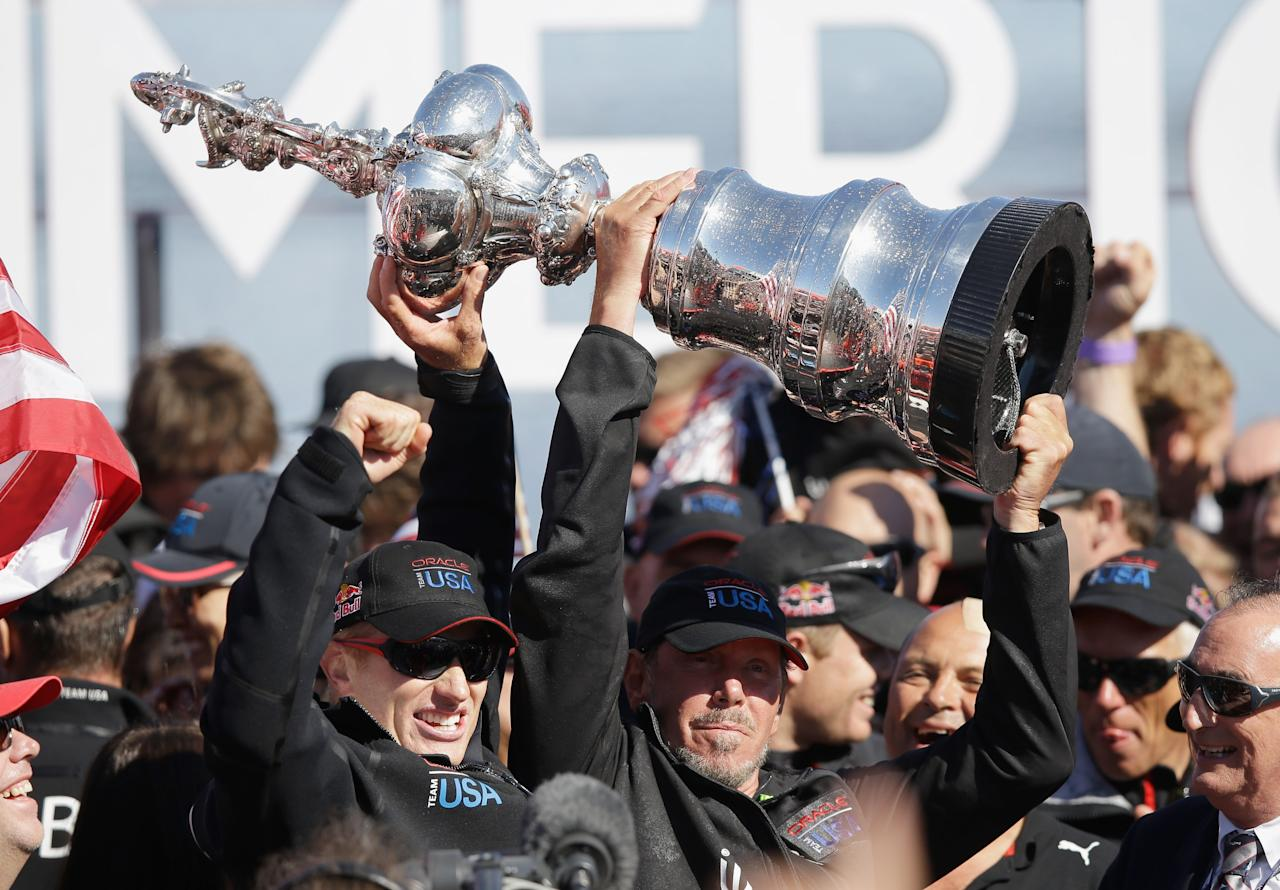 SAN FRANCISCO, CA - SEPTEMBER 25: Oracle Team USA skipper James Spithill and Oracle CEO Larry Ellison celebrate with the America's Cup trophy after they beat Emirates Team New Zealand skippered by Dean Barker in race 19 to win the America's Cup Finals on September 25, 2013 in San Francisco, California. (Photo by Ezra Shaw/Getty Images)