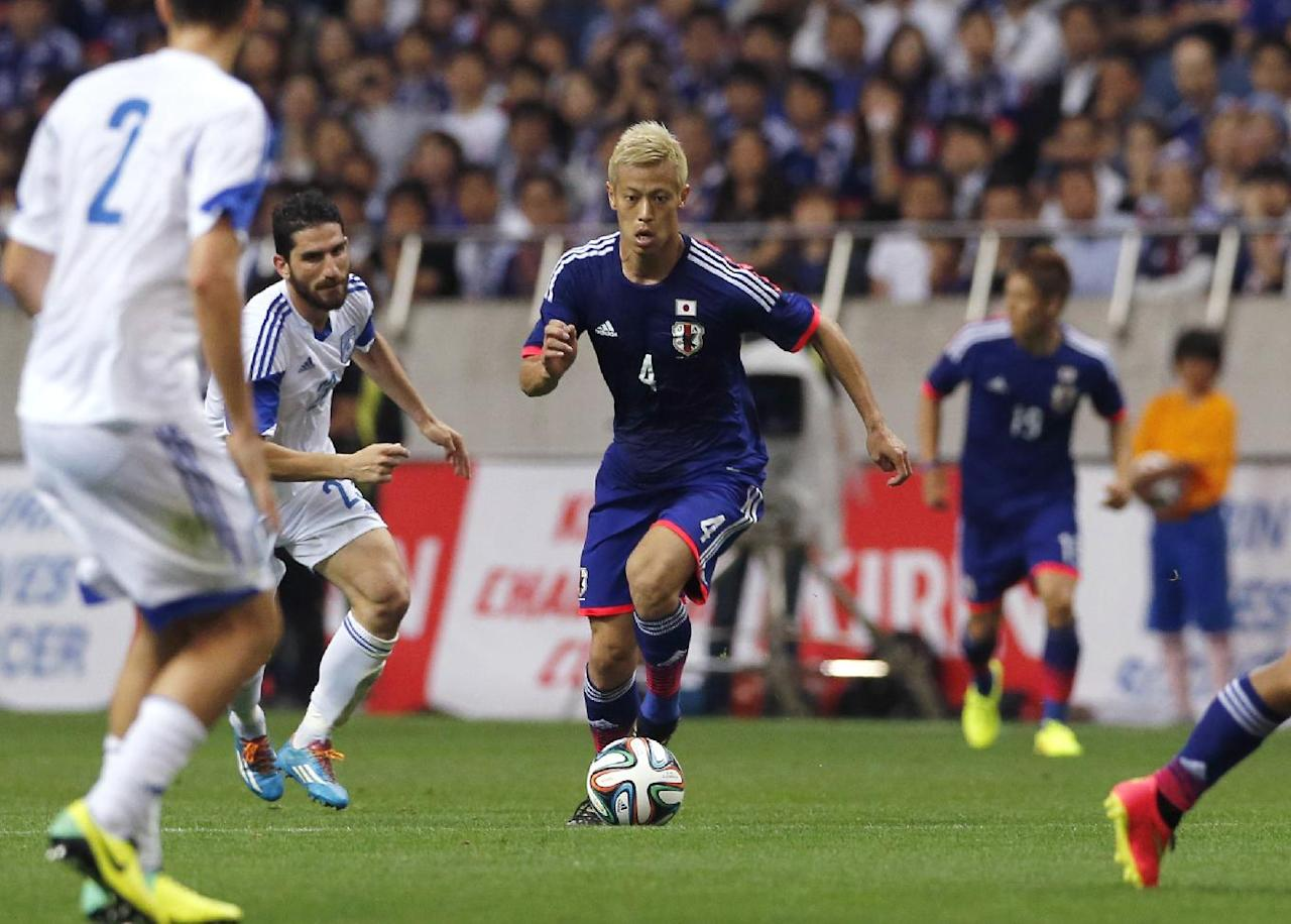 Japan's Keisuke Honda, center, controls the ball against Cyprus during a friendly soccer match in Saitama, north of Tokyo, Tuesday, May 27, 2014. Japan will play against Ivory Coast, Greece and Colombia in Group C of the World Cup 2014 in Brazil. (AP Photo/Shuji Kajiyama)
