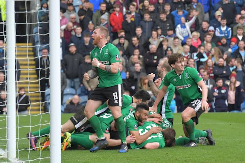 Lincoln City players celebrate after scoring against Premier League side Burnley in the fifth round of the FA Cup