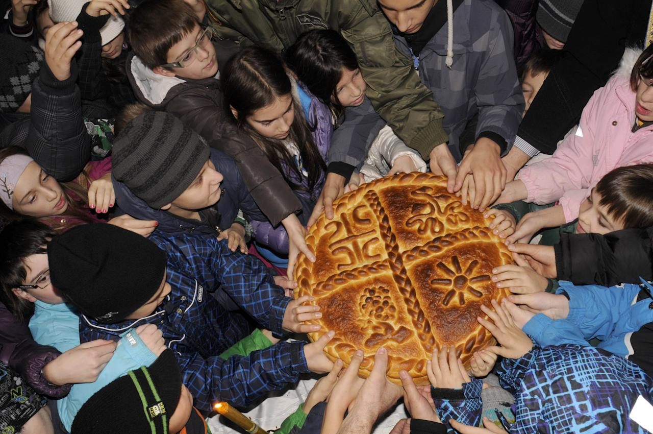 Bosnian Serb children break the traditional Christmas bread to mark Orthodox Christmas Day festivities, in front Orthodox Church in Banja Luka, 350 kms north west of Sarajevo, Monday, Jan. 7, 2013. (AP Photo/Radivoje Pavicic)