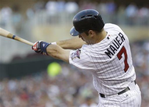 Minnesota Twins' Joe Mauer swings on an RBI single off New York Yankees pitcher Phil Hughes in the third inning of a baseball game, Tuesday, July 2, 2013 in Minneapolis. (AP Photo/Jim Mone)