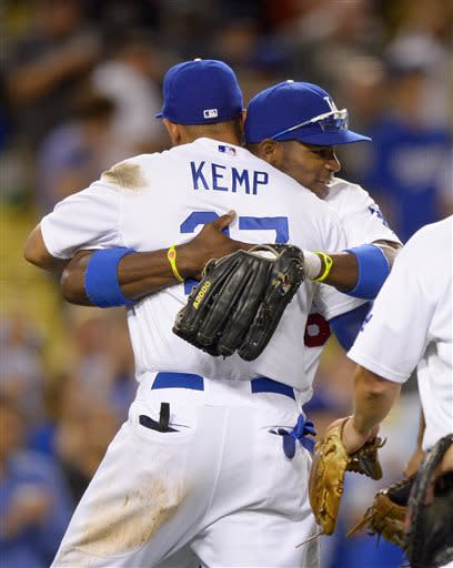 Los Angeles Dodgers right fielder Yasiel Puig, right, hugs center fielder Matt Kemp after Kemp made a catch on a ball hit by San Francisco Giants' Marco Scutaro to end their baseball game, Tuesday, June 25, 2013, in Los Angeles. The Dodgers beat the Giants 6-5. (AP Photo/Mark J. Terrill)