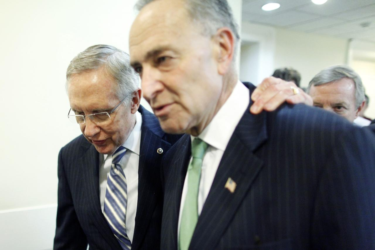 U.S. Senate Majority Leader Harry Reid (D-NV) (L) walks with his arm around Senator Charles Schumer (D-NY) as they depart following a news conference after bipartisan passage of budget and debt legislation at the U.S. Capitol in Washington, October 16, 2013. The U.S. Senate approved a deal on Wednesday to end a political crisis that partially shut down the federal government and brought the world's biggest economy to the edge of a debt default that could have threatened financial calamity. REUTERS/Jonathan Ernst (UNITED STATES - Tags: POLITICS BUSINESS)