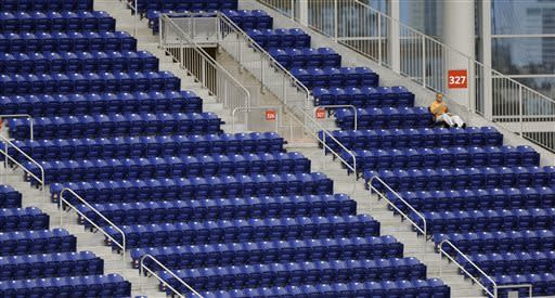 A fan sits in left field to watch a baseball game between the Atlanta Braves and the Miami Marlins in Miami, Tuesday, April 9, 2013. (AP Photo/J Pat Carter)