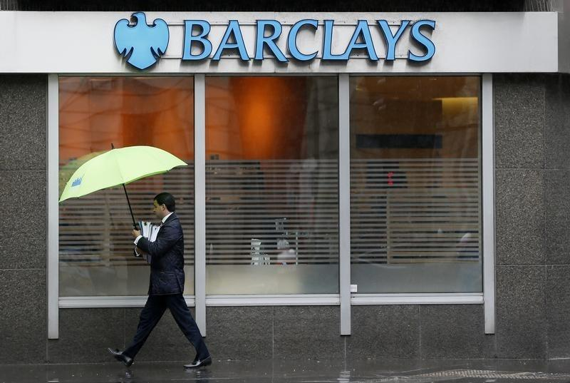 A man shelters under umbrellas as he walks past a Barclays branch in central London